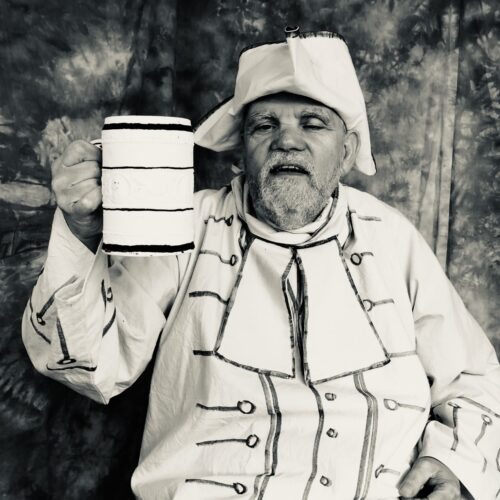 Black and white photograph of an older, bearded male actor wearing a white fabric Tricorn hat and 18th century style coat with a large necktie, holding up a large jug of ale in his right hand