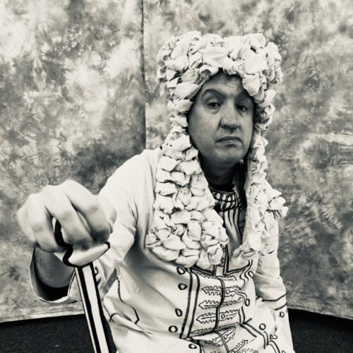 Black and white photo of a serious looking, seated male actor holding a walking cane and wearing a long 18th century style wig