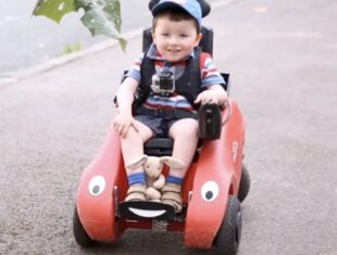 Still image of a young disabled child, sitting in a child's electric wheelchair