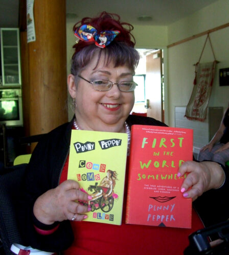 Portrait photo of a white woman holding up a copy of a bright red and yellow book