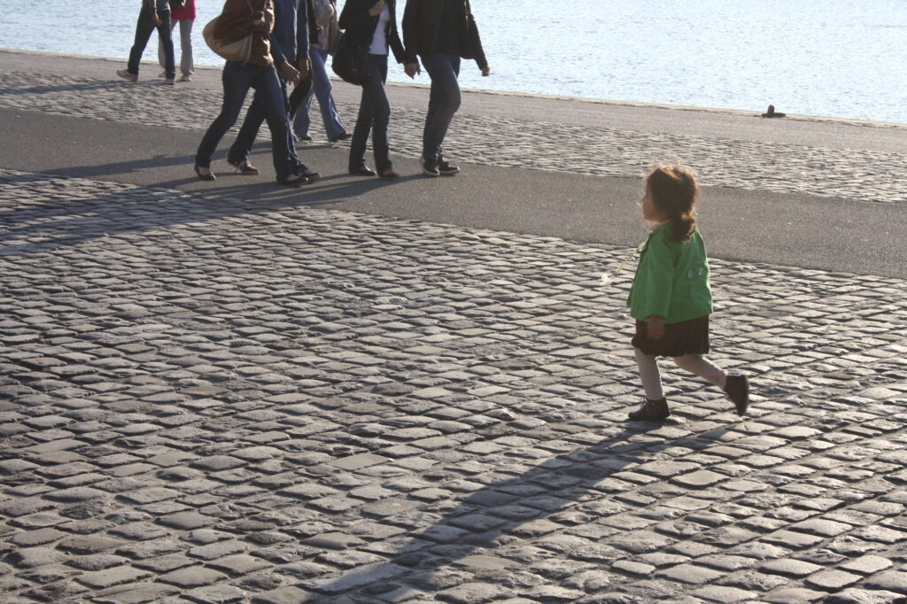 photo of a young white child walking alone on a promenade near the sea
