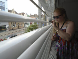 A young white woman wearing sunglasses, stands at a window looking through the slats of a white blind