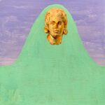 An image of a gold head sits upon a painted green hill with blue sky behind.