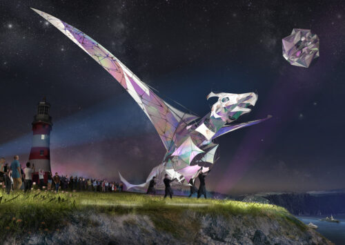 A puppet in the shape of a dragon is poised on a cliff top at night time, about to fly over the sea. There is a lighthouse behind and a crowd of onlookers