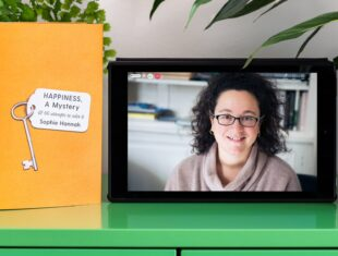 """Photograph of a tablet standing on a green cabinet next to two houseplants and a book. The book has a bright orange cover with an illustration of a key and white label. The book titles appear on the key's label in black text """"Happiness, A Mystery & 66 attempts to solve it"""" by """"Sophie Hannah"""". A photographic portrait of Sophie Hannah is on the tablet screen with video call icons """"People"""", """"Chat"""" and a red telephone icon."""