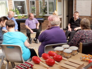 a photograph of disabled people participating in a music session