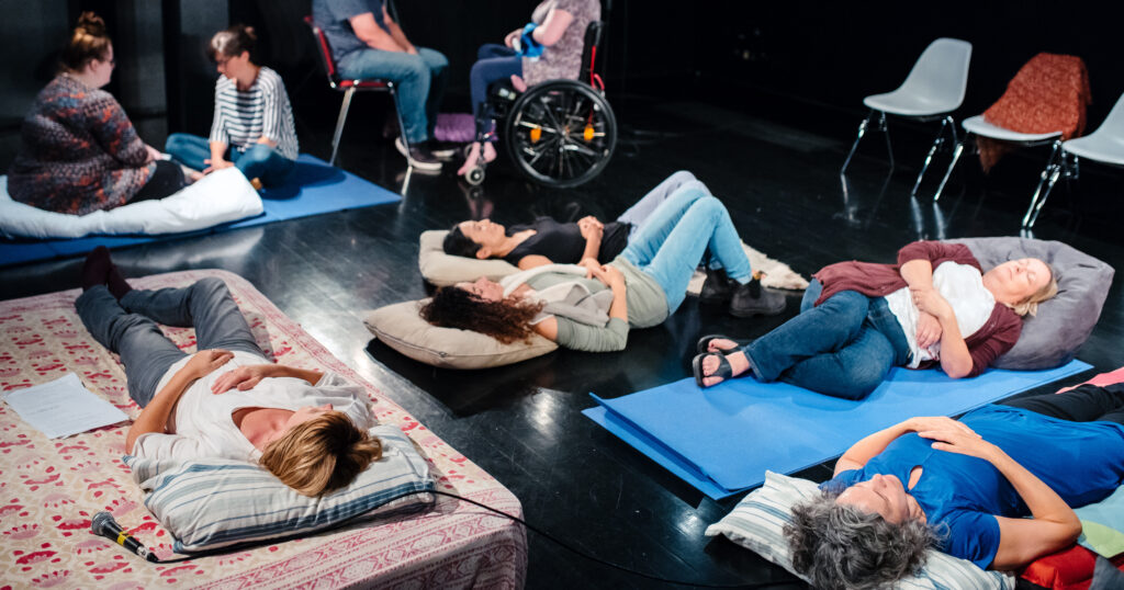 a group of people lie down on mattresses on a floor in a public space