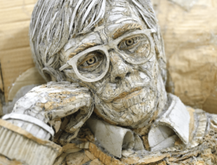 close up of cardboard sculpture showing a mans face learning on his hand