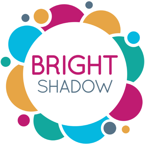A colourful circular logo of green, blue, orange and fuschia pink, with Bright Shadow in capital text in the middle.