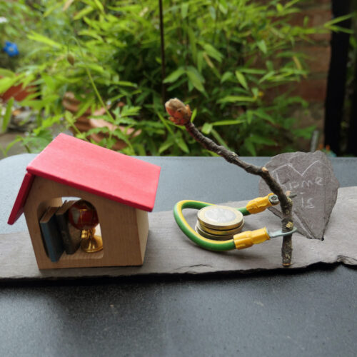Photo of an artwork consisting of a toy wooden house a branch with a budding flower, a few coins surrounded by a cable and a piece of slate with 'home is' scrawled within a heart