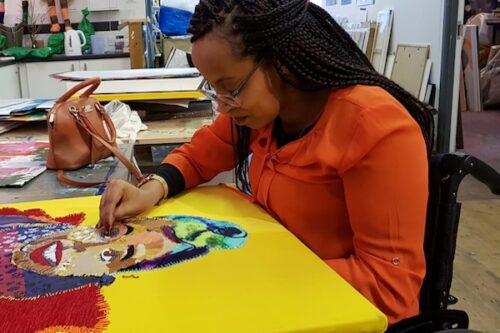 A woman of colour with long dark braided hair sits in a wheelchair working on a colourful textile artwork.