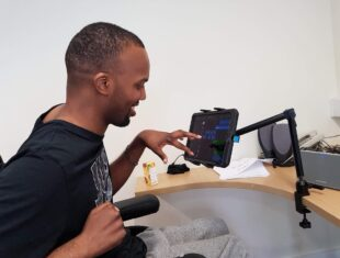 a young black man sits at a computer desk working with an iPad