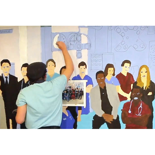 A man stands with their back to the camera, painting a group of medical staff on a large canvas.