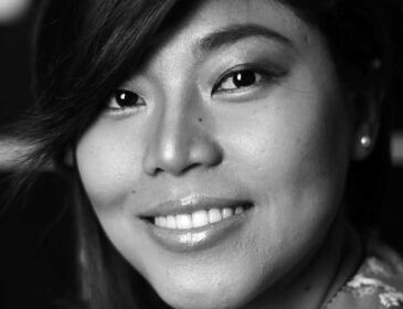 A black and white image of a Filipino woman smiling at the camera with shoulder length hair.