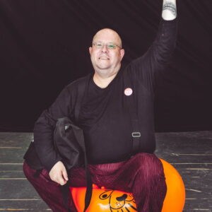 photo of a white, non-binary artist seated on an orange space hopper.