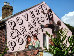 a photo of the wall mural regarding 'words not walls'. It shows several young people interacting with the words 'poverty can afford poetry' on the wall.