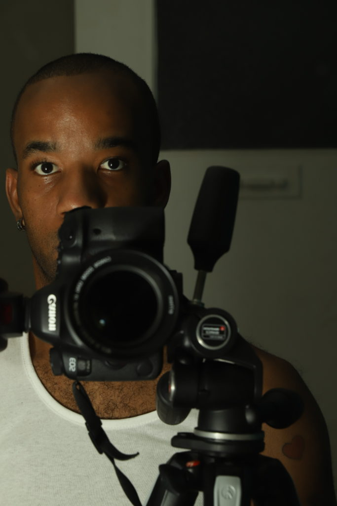 photo of a young black man posing behind a canon camera on a tripod