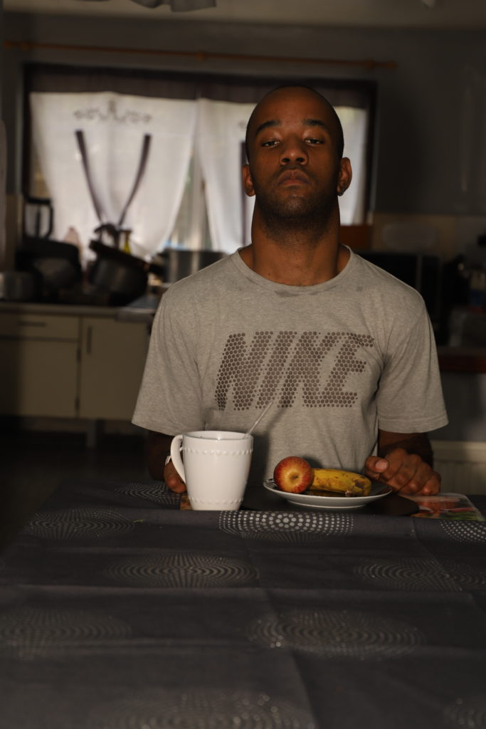 photo of a young black man sitting in a kitchen with fruit on a plate and a cup placed on a table in front of him
