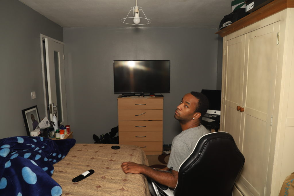 photo of a young black man sitting in a bedroom in front of a blank television, looking back at the camera