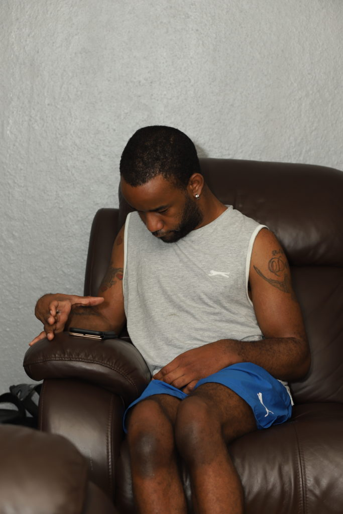 photo of a young black man sitting in an armchair, looking down at a smart phone placed flat on the arm of the chair