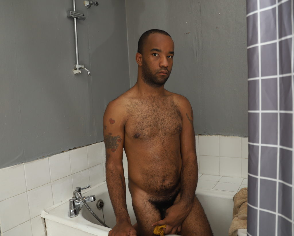 photo of a young black man standing, naked in a bath, looking askance at the camera