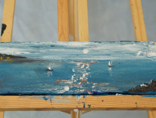 photo of a seascape painting on an easel