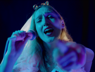Blonde woman with white hair holding a kareoke mic and pointing at the camera