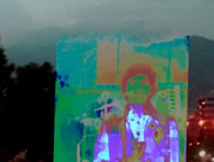 digitised portrait of a young male artist of colour standing, facing the camera, displayed through bright purple and green filters