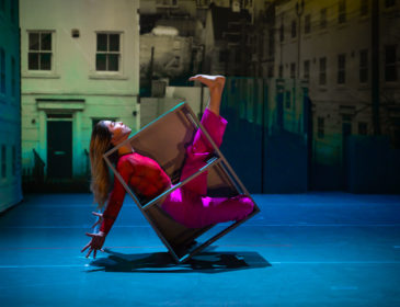 A solo dancer in pink leggings and red top is confined in a metal box-shaped frame about a metre high. The box is tilted back at 45 degrees, resting on one corner. The dancer's arms extend behind her, towards the floor, and she gazes calmly upwards as one leg kicks upwards, out of the frame. In the background, there are life-sized photographs of houses.