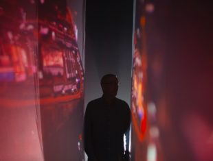 Photograph of a white man standing between two screens which are being projected on to