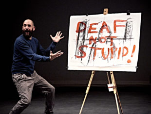Performer Jonny Cotsen standing on stage in front of a sign reading 'DEAF NOT STUPID'