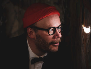 An image of '17' a white male wearing a red woollen hat, black framed glasses and a black dinner suit. '17' is peeking out of a hole up into the Big Blue.