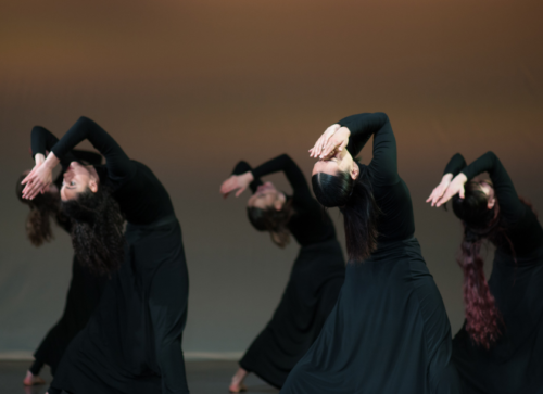 A group dressed in black all leaning over backwards with their hands over their faces.