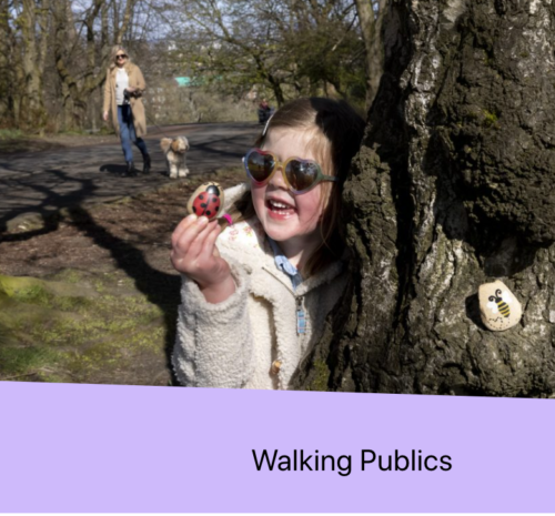 A child standing next to a large tree holding a stone with a ladybird painted on it. An adult and dog stand in the background. A purple stripe along the bottom of the photograph with black text 'walking publics'