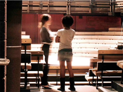 Two people stand in the empty Main House theatre space at the Young Vic Theatre. One of them stands side on, the other has their back to the camera. The figures are slightly blurred, as though in motion.