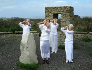 Pictured are five women standing inside a large stone circle, outside and with fields in the background. All the women are dressed entirely in white, and all have their hands positioned to the right of their face, one hand on the other, palms facing outward and up. A tall white rock is standing to the left, with one woman half concealed behind it.