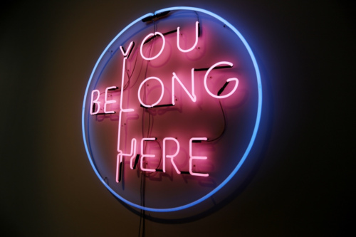A blue neon circle outline, with the text 'You Belong here' in pink neon within it.