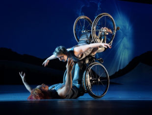 Laurel Lawson, a white woman with short cropped teal hair, is flying in the air with arms spread wide, wheels spinning, and supported by Alice Sheppard. Alice, a multiracial Black woman with coffee-coloured hair, is lifting from the ground below. They are making eye contact and smiling. A burst of white light appears in a dark blue sky. P
