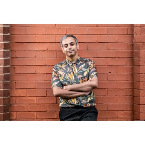 A photo of Shahid Iqbal Khan standing in front of a clay coloured brick wall, with his arms folded, smiling and looking straight to camera. He wears a floral shirt.