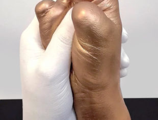 sculpture of a white hand grasping a gold coloured hand without digits