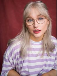 a young white woman with long blond hair wearing round glasses and a purple striped top