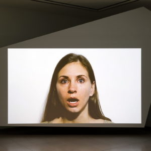 A screen suspended in a dark area showing the head of a woman with a shocked look on her face