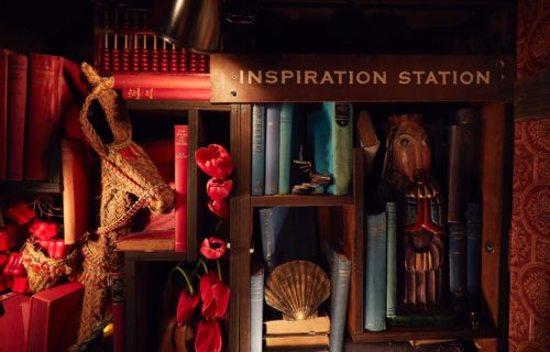 """A small library with """"Inspiration Station"""" labelled above. There are a collection of vintage books with some tulips perched between the shelves. There are collections of items scattered throughout the books such as a miniature man climbing a set of miniature stairs, a wooden doll, a shell and a wicker horse."""