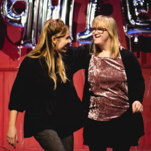 two young women are standing together on a stage with their arms around each other.