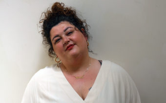 Mahalla is looking at the camera against a white background. Mahalla has black curly hair tied up, freckles, a gold nose ring, and gold hoop earrings.