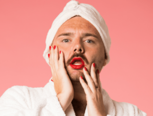 A man wears a white bath robe and towel, red lipstick and nail polish. He stands against a pink backdrop with his hands on his face.
