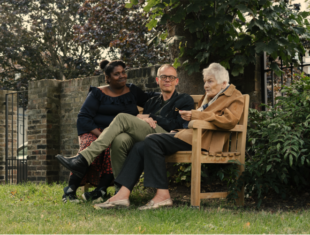 A young black woman and middle-aged white man are listening to an older woman - all three are sitting on a wooden bench in a garden.
