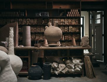 A photograph of an artists' workshop. In the centre is a large workbench with bags of clay piled beneath it. On top of the workbench is a large tan-coloured spherical clay sculpture with three tubular shapes protruding from its top. In the foreground are more vessel-like clay sculptures, ranging from burnt black to pale grey in colour. In the background, the walls of the workshop are covered in dark wooden shelves which are filled with terra cotta roof tiles. To the far right of the image, a white folding door is left ajar.