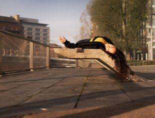 Woman lying down on a concrete bench