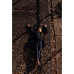 A view from above of a person laying on a concrete road with their arms above their head amongst fallen autumn leaves